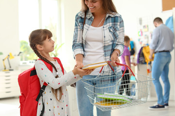 Little girl choosing school supplies with mother in stationery shop