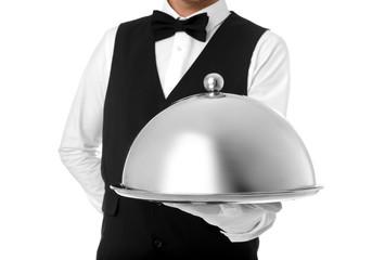 Fototapeta Waiter holding metal tray with lid on white background, closeup obraz
