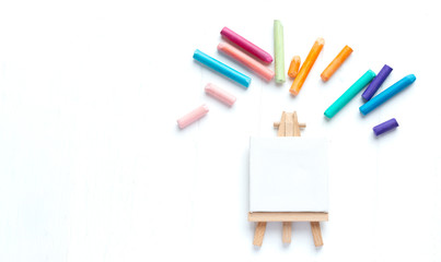 A small malbert with a clean canvas on a white background surrounded by colorful crayons. Template