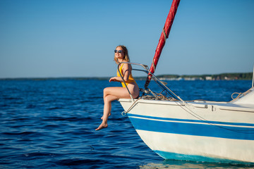Girl in sunglasses sitting on the bow of the yacht