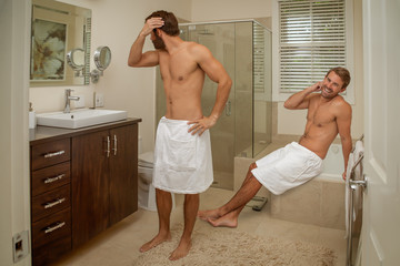A gay male couple in bath wraps is conversing in the bathroom.