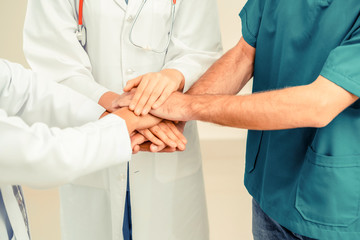 Doctor, surgeon and nurse join hands together.
