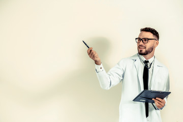 Male doctor points pen at empty wall copy space.