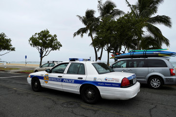 A Honolulu police car drives thru Ala Moana beach park warning beach goers as Hurricane Lane approaches Honolulu.