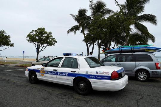 A Honolulu police car drives thru Ala Moana beach park warning beach goers as Hurricane Lane approaches Honolulu.