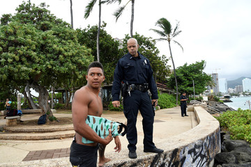 Honolulu police officer Chad Asuncion warns bodysurfer Kaimana Gomes about the water conditions as Hurricane Lane approaches Honolulu.