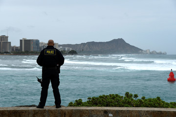 Honolulu police officer Chad Asuncion monitors the water conditions and warns surfers about the conditions as Hurricane Lane approaches Honolulu