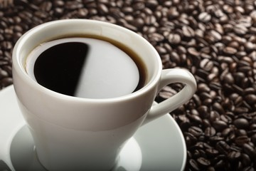 Closeup of cup of coffee and coffee beans