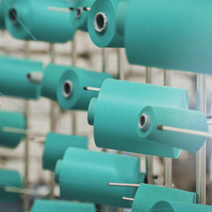 Modern Textile Factory. Rows of automated machines for yarn manufacturing.