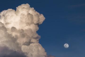 Storm cloud near full moon over blue sky