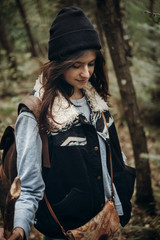 beautiful hipster traveler smiling, walking in woods. stylish woman hiking. wanderlust and travel concept