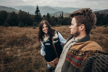 happy hipster traveler couple taking selfie on top of mountains and laughing. wanderlust and travel concept with space for text. emotional moment of stylish family