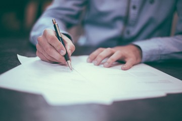 Man signing a contract on table, writing with a pen, signing on a paper, writing document, work, tax, corporate, business