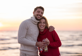 Couple hugging and drinking beer together at the beach