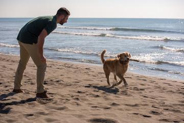 man with dog enjoying free time on the beach