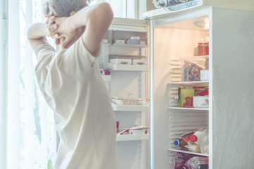 young man searching for food in the fridge at home