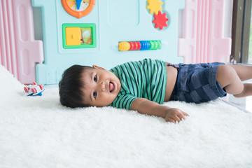 Cute little baby boy lying on soft blanket