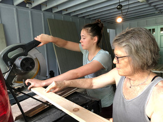 Jean O'Neill and her daughter Ceri Godinez measure and cut wood to board up their house in Hanalei on Kauai Hawaii