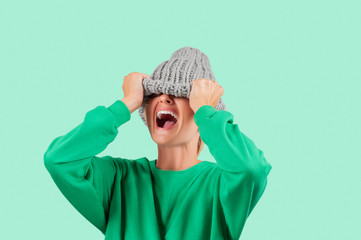 Crying emotional angry woman is pulling wool hat over her eyes