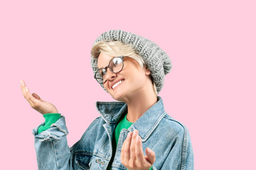 Happy beautiful woman in fashionable jeans jacket and hat on pink background.