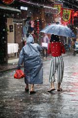 Walking in the rain down west street Yangshuo China