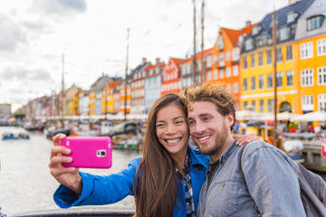 Wall Mural - Copenhagen travel couple tourists taking selfie photo with phone camera. Smiling young people students at old port Nyhavn, tourism danish landmark in Denmark, northern Europe.