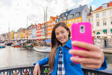 Selfie tourist girl taking photo with phone at Copenhagen Nyhavn, famous Europe tourism attraction. Asian woman visiting the old town waterfront water canal in Kobenhavn, Denmark, Scandinavia.