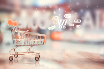 Shopping cart on table with financial market icon background