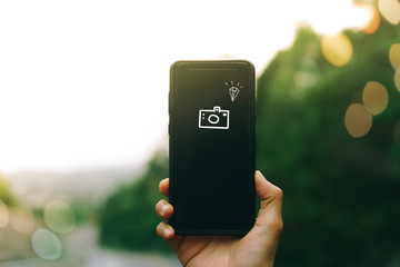 Woman hand using smartphone to take a photo of beautiful scene for on high road sun light bokeh background.