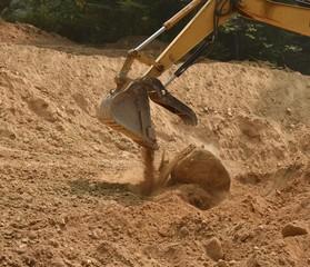 Trackhoe bucket dropping large heavy boulder