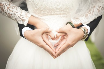 Couple forming a heart shape with their hands wedding marriage love valentines bride groom dress suit hands couple