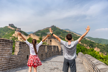 China travel at Great Wall. Tourists couple happy cheering in Asia on famous Chinese tourist attraction in Beijing. Young people with arms up in success visiting Great Wall enjoying summer vacations.