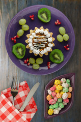 dessert of cake and fruit (grapes, kiwi, pomegranate) on a wooden