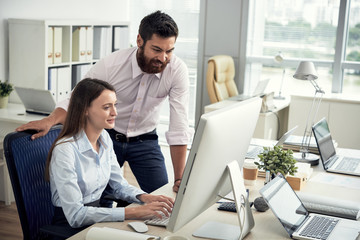 Smiling businessman helping young female colleague with work