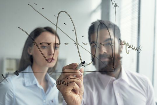Businessman drawing chart on glass wall to explain his idea to coworker
