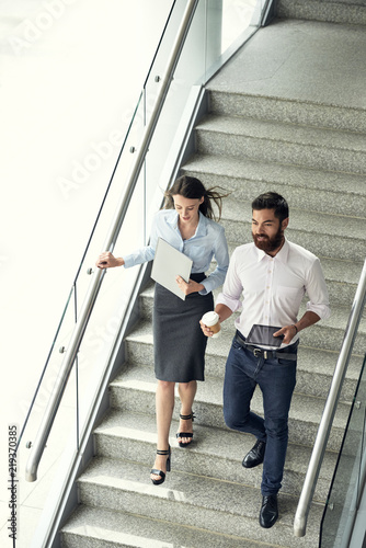 Young Business Couple Going Down The Stairs In Office Building View