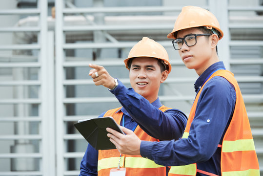 Young professional engineers discussing problem on production facility