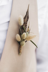 Groom boutonniere with feather and dried wildflowers in boho style on beige waistcoat
