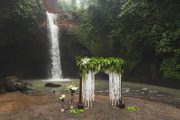 Tropical wedding ceremony with waterfall view. White arch decorated with green jungle leaves monstera and fern