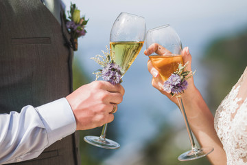 Man and woman hands holding two champagne glasses decorated with flowers for wedding ceremony