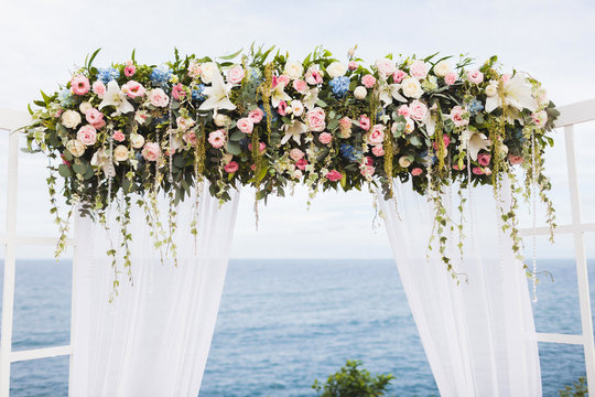 Wedding ceremony on cliff with sea view in light white tones, wooden arch and flower decoration