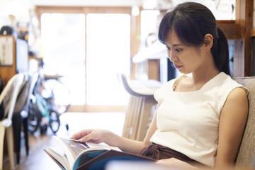 カフェでくつろぎながら読書を楽しむ女性