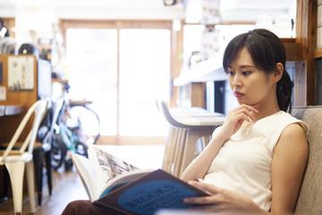 カフェでくつろぎながら本を読む女性
