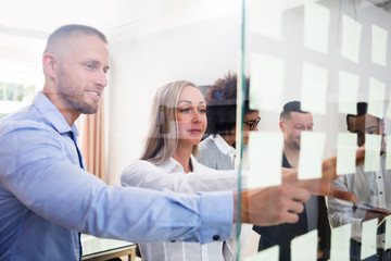 Group Of Businesspeople Sticking Adhesive Notes On Glass Wall