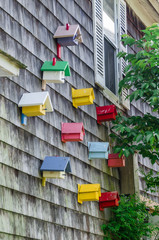 Photograph of some bird houses plastered on the wall of a house on Long Island, New York.