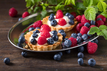 Dessert tarts with raspberries and blueberries on a wooden table.