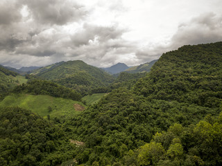 Aerial view of a village in the lush green rain cloud cover tropical rain forest mountain during the rainy season on the Doi Phuka Mountain reserved national park the northern Thailand
