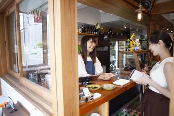 カフェのレジカウンターで楽しそうに話している女性とスタッフ