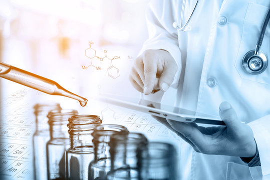 Doctor using tablet with lab glassware background