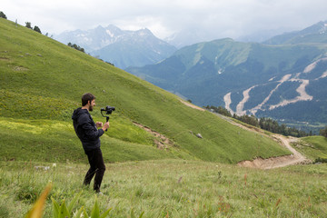 guy kameraman in a jacket stands in the mountains on a green meadow and shoots a video on Steadicam